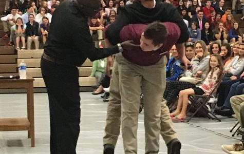 One student tries to walk while bearing the weight of the other student in a demonstration about forgiveness.