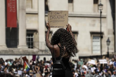A woman holds up a banner as people gather in Trafalgar Square in central London on Sunday, May 31, 2020 to protest against the recent killing of George Floyd by police officers in Minneapolis that has led to protests across the U.S.